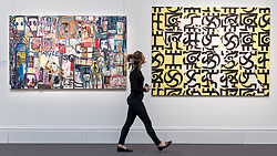 "© Licensed to London News Pictures. 29/03/2019. LONDON, UK. A staff member walks by (L to R) ""Untitled"" by Abdoulaye Aboudia Diarrassouba (Est. GBP 8,000-12,000) and ""Movement No. 1"", 1995, by Owusu-Ankomah (Est. GBP 15,000-20,000).   Preview of Sotheby's upcoming Modern and Contemporary African Art sale.  Works from artists across the African diaspora will be offered for sale on 2 April.  Photo credit: Stephen Chung/LNP"