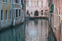 view in Venice with incoming gondola on water reflections late in the afternoon in fall