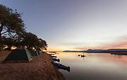 Canoe safari camp at sunset by lower Zambezi River in Mana Pools National Park, Zambia