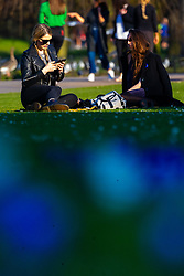 Friends Eden, left, 22 and Carolyn, 22 take a break on the lawn as crowds enjoy the unseasonably warm and sunny weather in Regents Park, London. London, February 26 2019.
