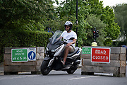 A moped rider illegally passes through the barriers that form an LTN (Low Traffic Neighbourhood), an experimental closure by Southwark Council preventing motorists from accessing the junction of Carlton Avenue and Dulwich Village. Restrictions also prevent traffic from passing through at morning and afternoon rush-hour times in the borough of Southwark, on 14th June 2021, in London, England.