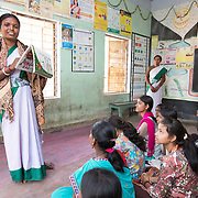 CAPTION: Sahiya Anupma Soren quizzes the girls on such subjects as the legal age of marriage, their daily nutritional needs and the foods that can provide these, the sort of medical advice that's available for them, etc. There are two groups in the room. One is made up of married adolescents, aged 15-19, which discusses delaying the age of marriage, the different methods of family planning that are available, and antenatal care; the other consists of 10 to 14-year olds, with some school-going girls and some school dropouts, and this group focuses in a big way on nutrition, menstrual hygiene, and developmental changes. LOCATION: Pawra Anganwadi Centre (AWC), Ghatshila (block), Purbi Singhbhum (district), Jharkhand (state), India. INDIVIDUAL(S) PHOTOGRAPHED: Anupma Soren (standing, left) and multiple others.