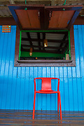 Cafe exterior with chair and window in blue wall, Little Corn Island, Nicaragua
