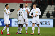 Wilfried Bony of Swansea city (2) is congratulated by teammates Martin Olsson (l), Mike van der Hoorn © and Alfie Mawson ® after the game. Premier league match, Swansea city v West Bromwich Albion at the Liberty Stadium in Swansea, South Wales on Saturday 9th December 2017.<br /> pic by  Andrew Orchard, Andrew Orchard sports photography.