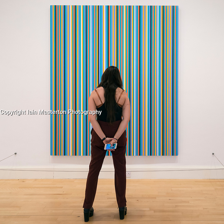 Woman looking at painting Apres midi by Bridget Riley on display at Scottish National Gallery of Modern Art in Edinburgh, Scotland, United Kingdom