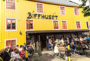 Biffhuset pub with people drinking in summer sunshine outdoors, Tromso, Norway