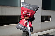 Man carrying a large shopping bag almost the same size as himself, London, UK.
