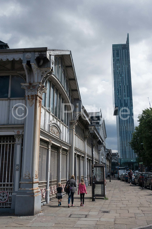 A young family walk past the Upper Campfield Market Hall on Liverpool Road with views of Beetham Tower on the 10th August 2018 in Manchester in the United Kingdom. Beetham Tower is a landmark 47-storey mixed use skyscraper, while The former Upper Campfield Market Hall was built in 1876 and is a Listed Grade II building. It is now the Air and Space Hall at the Manchester Museum of Science and Industry.