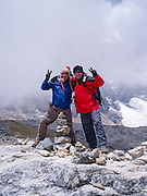 A pair of Peruvian hiking guides celebrates their achieving their arrival at Salkantay Pass, along Camino Salkantay, near Soraypampa, Peru, with Montaña Salkantary in the background.