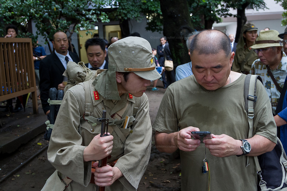 A young Japanese man in Imperial Army uniform checks the smart phone of a friend as Yasukuni shrine marks the 72nd anniversary of the end of the Pacific War. Yasukuni Shrine, Kudanshita, Tokyo Japan. Tuesday August 15th 2017. Nominally a event to honour Japan's war dead and call for continued peace, this annual gathering  at Tokyo's controversial Yasukuni  Shine also allows many Japanese nationalists to display their nostalgia for their Imperial past.Rightwing paramilitary groups, Imperial cos-players, politicians and many ordinary citizens come together at the shrine to march and wave flags. The day goes almost unreported in the mainstream Japanese media.