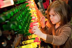 "United States, Washington, Bellevue, KidsQuest Children's Museum, girl inserting pegs at ""Lite it Up"" exhibit"