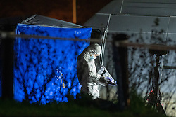 © Licensed to London News Pictures. 07/02/2021. Reading, UK. A forensic investigator stands next to blue forensic tent and a white van. At approximately 18:55GMT on Saturday 06/02/2021 Thames Valley Police were called to reports of an altercation in Dulnan Close, Tilehurst in Reading. A 25-year-old man sustained multiple injuries and died at the scene. Photo credit: Peter Manning/LNP