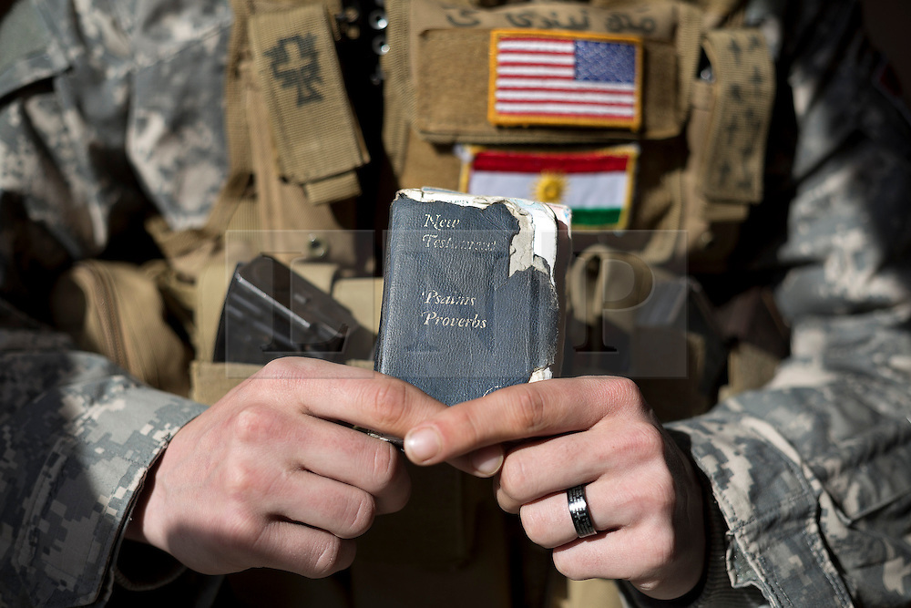 © Licensed to London News Pictures. 19/02/2015. Dohuk, Iraq. Brett, an American volunteer fighter with the Dwekh Nawsha Christian militia, is pictured holding his bible at a house in Dohuk, Iraqi-Kurdistan. A portrait of Brett, an American volunteer fighter serving with the Dwekh Nawsha Christian militia, taken in Dohuk, Iraqi-Kurdistan. Photo credit : LNP