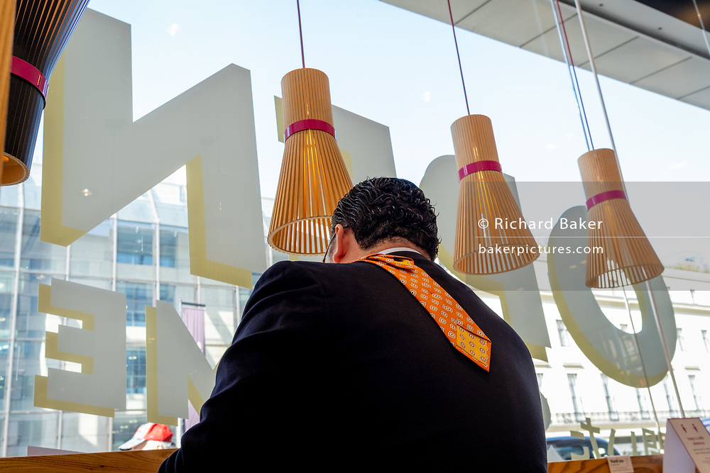 A rear view of a man eating his lunch with his orange tie laying over his shoulder and down his back, at the Strand West End branch of Sushi restaurant, ITSU, on 28th September 2020, in London, England.