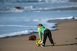 A young child playing with a toy on the beach at Fistral in Newquay, Cornwall.