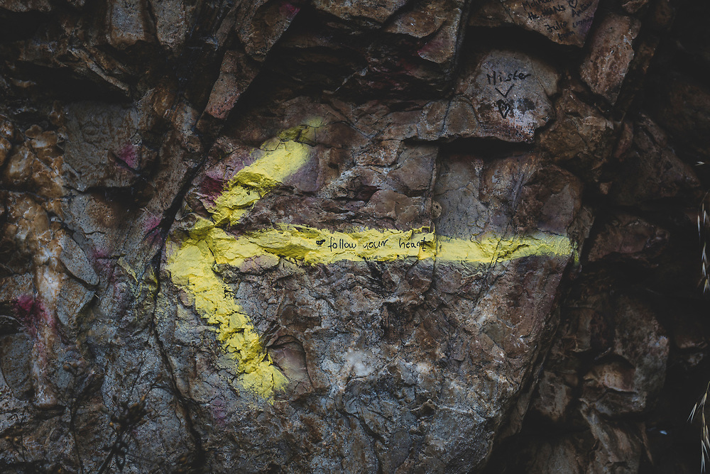 A yellow arrow, a sign of the Camino's direction, is painted on a rock wall as the path ascends into the mountains above Villafranca del Bierzo. (July 3, 2018).<br /> <br /> DAY 37: VILLAFRANCA DEL BIERZO T0 LA FABA -- 24 KM