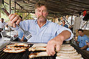 29 JULY 2007 -- BRUNIG, OBWALDNER, SWITZERLAND: A man grills bratwurst for spectators during the Brunig Schwinget, a wrestling tournament in Brunig, in the canton of Obwaldner, Switzerland. Schwingets are Swiss style wrestling tournaments held throughout Switzerland. They are usually held outdoors in Alpine mountain passes. Wrestlers wear special canvas pants over their regular clothes. They grip each others pants and wrestle on bed of sawdust. The Schwinget in Brunig is one of the most popular in Switzerland with over 6,000 spectators and more than 120 wrestlers. There is Swiss Alpenhorn blowing, flag throwing and yodeling at the Schwinget.  Photo by Jack Kurtz