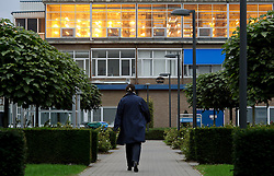 A Philips employee walks towards a building housing a light testing lab on the top floor, at the Philips Lighting factory campus, in Turnhout, Belgium, on Friday, Oct. 15, 2010. (Photo © Jock Fistick)