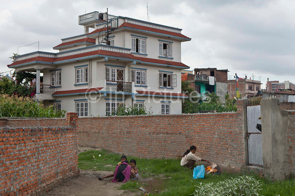 Women and young children play outside the walled compound of GoodWeave Foundation's new centre in Attarkhen, Kathmandu, Nepal.  GoodWeave is a charity that works toward getting young children out of carpet factories and into education. This centre is focused on finding new lives for children removed from the factories. GoodWeave were recipients of the Stars Foundation's Impact Award.