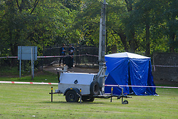 © Licensed to London News Pictures. 13/10/2021. London, UK. A forensic tent on Craneford Way Playing Fields as officers work in the background following the fatal stabbing of a teenager. Police were called at 16:45BST on Tuesday, 12 October to reports of a stabbing in Craneford Way, Twickenham. Metropolitan Police Service (MPS) and London Ambulance Service (LAS) attended. They found an 18-year-old man who is believed to have sustained knife wounds. He was taken by LAS to an outer London hospital where he was pronounced dead at 17:54BST. Photo credit: Peter Manning/LNP