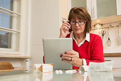 Senior woman reading package insert for pills on digital tablet, Munich, Bavaria, Germany