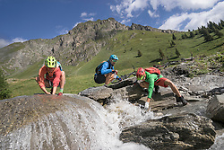 Three mountain biker friends drinking water in stream, Zillertal, Tyrol, Austria
