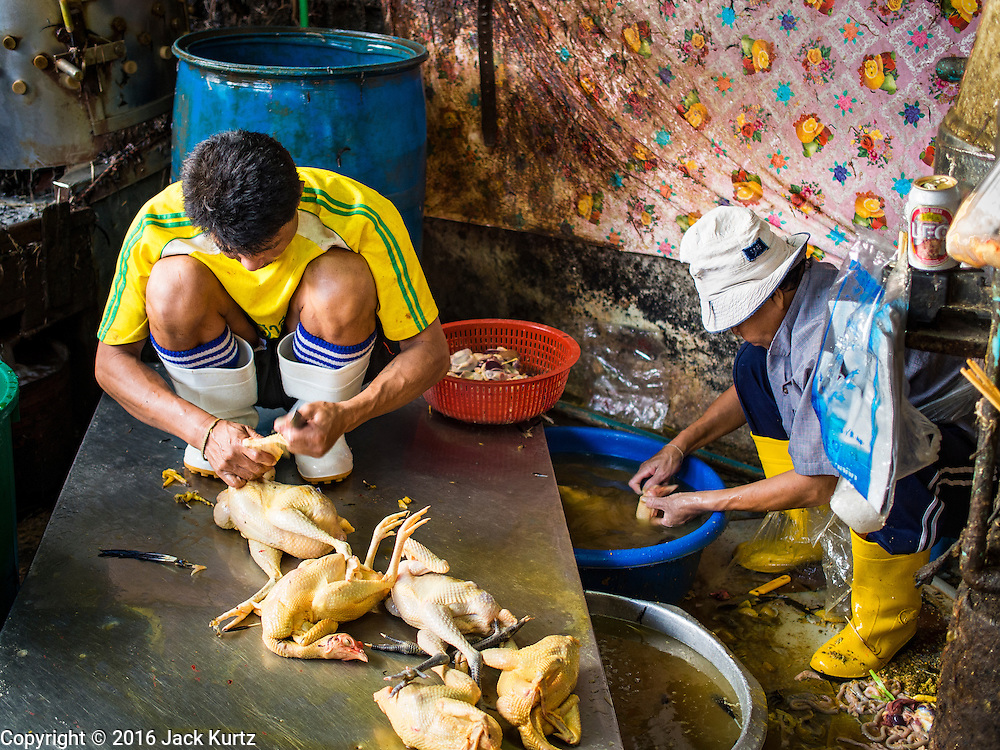 "12 JANUARY 2016 - BANGKOK, THAILAND: Workers slaughter chickens in the live poultry section of Khlong Toey Market (also spelled Khlong Toei) in Bangkok. On Monday the Thai Ministry of Public Health instructed government agencies to watch for any signs of ""bird flu"" during the winter season, and warned the public to avoid contact with any birds that appear sickly. The latest data from the World Health Organization showed the continuous transmission of avian flu in various countries, both in people and birds. Bird Flu is endemic in China, Vietnam and Indonesia, all important Thai trading partners. There have been no recorded outbreaks of Bird Flu in humans in Thailand several years.      PHOTO BY JACK KURTZ"