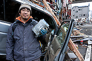 Juinichi Kano who lost his wife and mother in the tsunami that struck north east Japan on March 11th collects some personal affects from his wrecked car in Kamaishi, Iwate, Japan. March 17th 2011