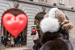 """© Licensed to London News Pictures. 14/02/2018. LONDON, UK. A tourist takes a photo of a giant chubby heart balloon at The Ritz Hotel in Piccadilly as part of """"Chubby Hearts Over London"""",  a design project conceived by Anya Hindmarch.  Supported by the Mayor of London, the British Fashion Council and the City of Westminster giant chubby heart balloons will be suspended over (and sometimes squashed within) London landmarks as a declaration of love to the city starting on Valentine's Day and continuing throughout London Fashion Week.  Photo credit: Stephen Chung/LNP"""