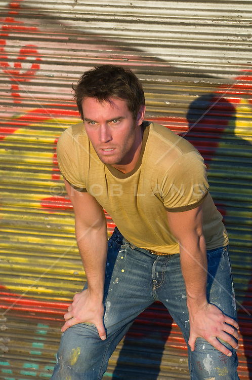 man leaning forward on his knees in front of a graffiti gate