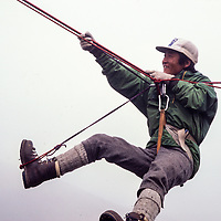 Nima Tsering Sherpa practices a Tyrolean traverse at an early mountaineering school for sherpas in the Khumbu region of Nepal, 1980.