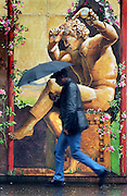A mural shows a different story as the rain comes down on a pedestrian in downtown Sacramento.