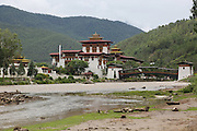 Punakha Dzong, Punakha, Bhutan..Bhutan the country that prides itself on the development of 'Gross National Happiness' rather than GNP. This attitude pervades education, government, proclamations by royalty and politicians alike, and in the daily life of Bhutanese people. Strong adherence and respect for a royal family and Buddhism, mean the people generally follow what they are told and taught. There are of course contradictions between the modern and tradional world more often seen in urban rather than rural contexts. Phallic images of huge penises adorn the traditional homes, surrounded by animal spirits; Gross National Penis. Slow development, and fending off the modern world, television only introduced ten years ago, the lack of intrusive tourism, as tourists need to pay a daily minimum entry of $250, ecotourism for the rich, leaves a relatively unworldly populace, but with very high literacy, good health service and payments to peasants to not kill wild animals, or misuse forest, enables sustainable development and protects the country's natural heritage. Whilst various hydro-electric schemes, cash crops including apples, pull in import revenue, and Bhutan is helped with aid from the international community. Its population is only a meagre 700,000. Indian and Nepalese workers carry out the menial road and construction work.