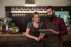 Confident restaurant owners discussing while using digital tablet