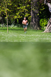 A shirtless man runs in the dappled sunshine on a perfect spring day in Regents Park. London, May 04 2018.