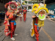 26 AUGUST 2014 - BANGKOK, THAILAND: A troupe of Lion Dancers go business to business looking for donations on Sukhumvit Soi 63 (Ekkamai). The dancers would perform at businesses who paid them a small fee. The performance is supposed to bring good luck and prosperity in the coming year.     PHOTO BY JACK KURTZ