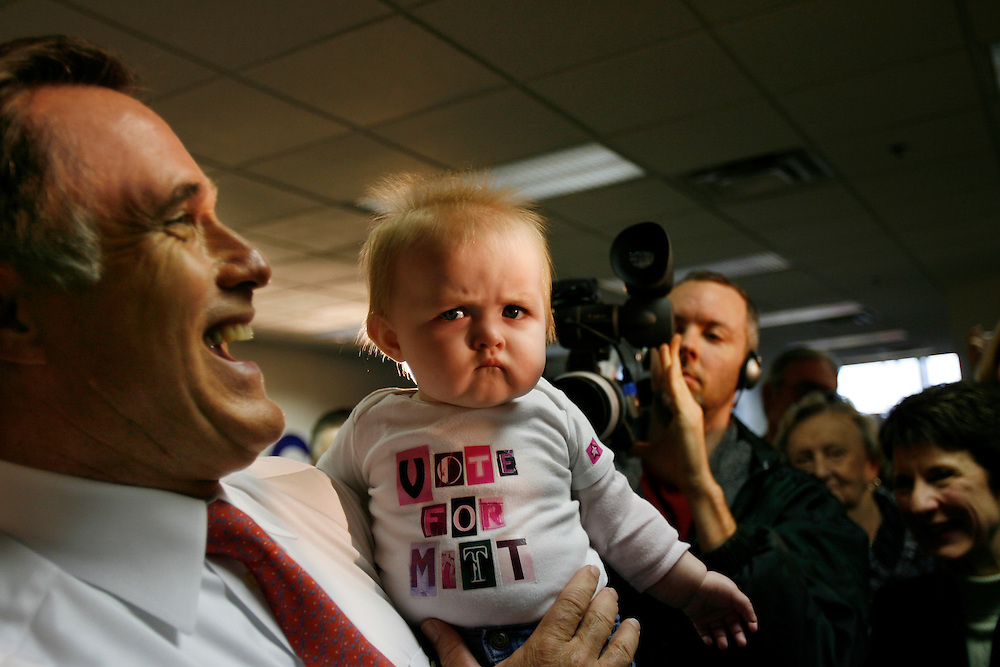 """Governor Mitt Romney laughs as he holds a very reluctant Mackenzie Branstad, 9 months, of Des Moines at an event to open his new Iowa Campaign Headquarters in Urbandale, Iowa.  Mackenzie was wearing a """"Vote For Mitt"""" t-shirt."""