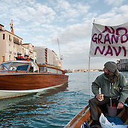 """VENICE, ITALY - JANUARY 16:  A protester, sailing next to a Coast Guard power boat on the Grand Canal, holds black listed banner reading """"Stop the large Ships""""  on the day of the special meeting discussing the environmental impact of cruises in Venice on January 16, 2012 in Venice, Italy. Protest are mounting in Venice against large cruise ships crossing St Marks's basin after the Costa Concordia tragedy."""