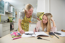 Mother helping daughter with homework, smiling