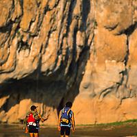 Expedition climbers returning to camp along river beach, Ban Pak Ou, Luang Phrabang, Laos