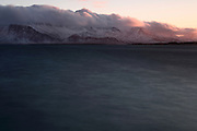 The rising sun is reflected on clouds over the mountains that lie north of the bay in which Reykjavik sits. Long exposure shot.