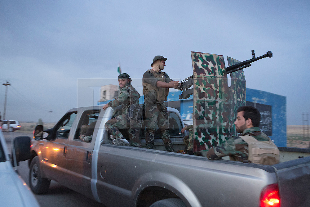 © Licensed to London News Pictures. 30/09/2015. Kirkuk, Iraq. Kurdish peshmerga fighters travel in the back of a pickup truck armed with a heavy machine gun as they prepare to take part in an offensive to capture 7 villages from the Islamic State near Kirkuk, Iraq.<br /> <br /> Supported by large amounts of coalition airstrikes, members of the Iraqi-Kurdish peshmerga today (30/09/2015) took part in an offensive to take seven villages across a large front near Kirkuk, Iraq. By mid afternoon the Kurds had reached most of their objectives, but suffered around 10 casualties all to improvised explosive devices. All seven villages were originally Kurdish and settled with other ethnic groups during the Iraqi Arabisation process of the 1970's and 80's. Photo credit: Matt Cetti-Roberts/LNP