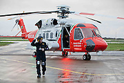 Crew Member Ciaran McHugh in front of the  new Coast Guard Sikorsky S-92 helicopter which arrived at Shannon airport today with the older S-61 Coast Guard helicopter in the background. Photograph by Eamon Ward (Pat Flynn has sent story)