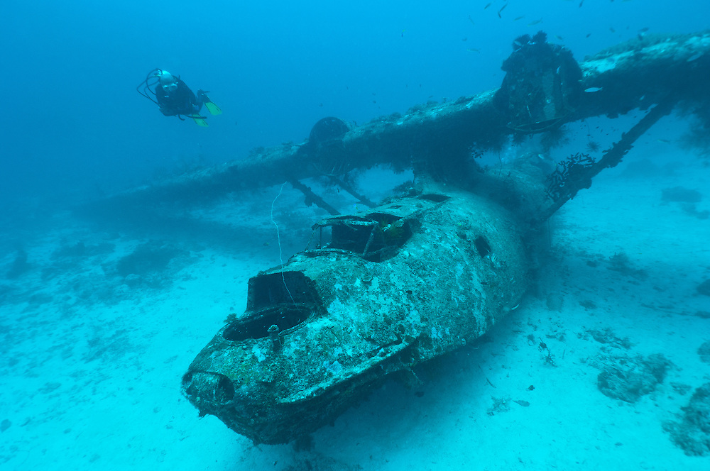 Diver exploring the wreck of a PBY Catalina seaplane or flying boat underwater, Biak, West Papua, Indonesia.