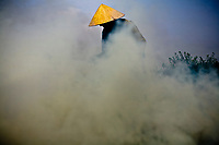 """A farmer burns off crop residue to prepare for the post-flood planting season in Hanoi, Vietnam. This kind of """"purging"""" on farmlands across Vietnam continues to cause damage to air quality and the local environment."""