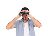 Young man in his early 20s looking through a binoculars looking at camera