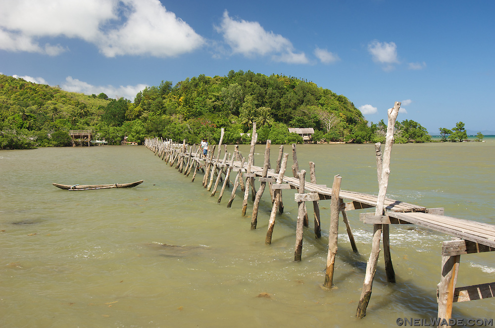 Two men cross a rickety hand made bridge on Palawan island in Taytay, Philippines.