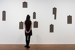 """© Licensed to London News Pictures. 17/04/2018. LONDON, UK. A staff member views """"Evolutionare Schwelle (Threshold of Evolution)"""", 1985, 8 felt pieces, uniquely cut, at the preview of """"Joseph Beuys: Utopia at the Stag Monuments"""", at the Galerie Thaddaeus Ropac in Dover Street.  The retrospective is the most important UK exhibition of Beuys' work in over a decade, presenting major sculptures and rarely seen works from 1947 to 1985, and runs from 18 April to 16 June.  Photo credit: Stephen Chung/LNP"""