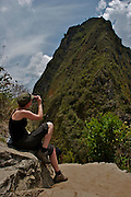 A tourist is taking a photograph of the mountain of Waynapicchu, just in front of the famous Machu Picchu