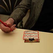Elderly man playing bingo at Adlington Community Centre, Parson Cross, Sheffield, South Yorkshire, UK